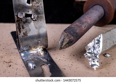 A large soldering iron and soldering accessories on a workshop table. Connecting sheets using soldering. Dark background.