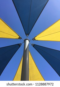 Large solid weatherproof commercial strength sun shade canopy sail for playgrounds and parks in blue and yellow symmetrical pattern