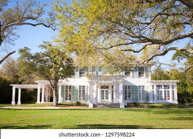 Large Southern style home in America featuring large windows, shutters and a porch. Oak trees frame the exterior of the house.
