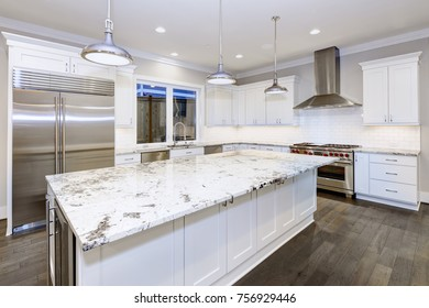 Large, spacious kitchen design with white kitchen cabinets, white kitchen island with lots of storage, white Granite countertops, subway tiles and stainless steel appliances. Northwest, USA