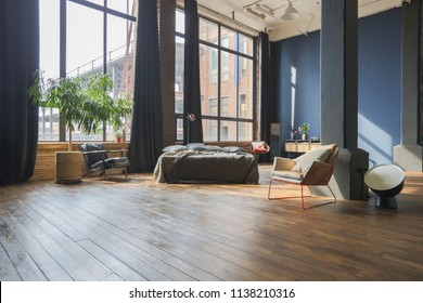 Large spacious loft room in dark colors in the rays of sunlight with big window. free lay-out.