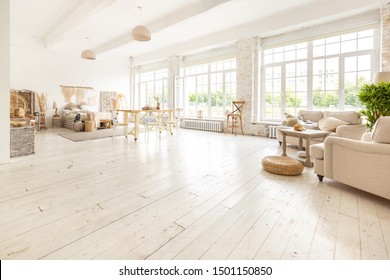 Large spacious room with a trendy loft design of sitting area. huge windows and stylish wicker light furniture inside.  an abundance of ethnic decor
