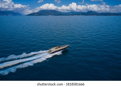 Large speedboat moving at high speed in the background of the coastline mountains and cumulus clouds. The boat is gray-blue combined color. Large speed boat moving at high speed side view.