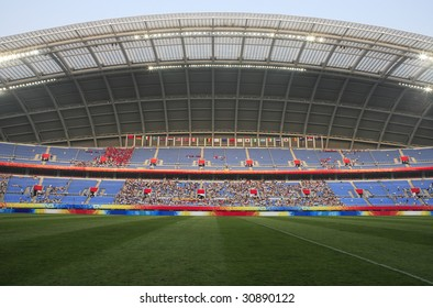 A large sports stadium filling with fans before the start of a soccer match.