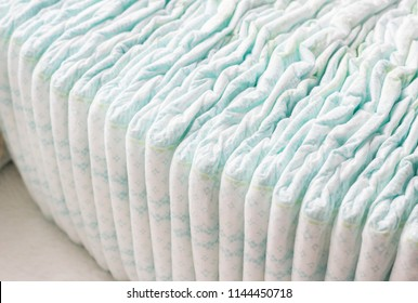 A large stack of baby diapers, close-ups, diaper packaging