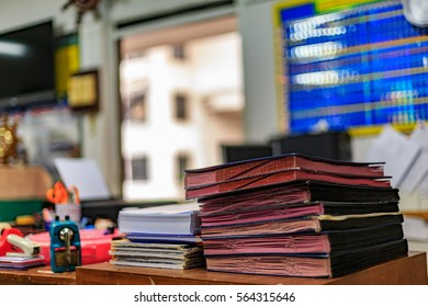 A large stack of business files, documents, reports, and desks.