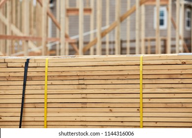 A large stack of roofing trusses laying on the ground with shallow depth of field