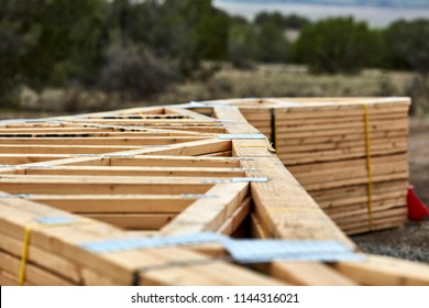 A large stack of roofing trusses laying on the ground