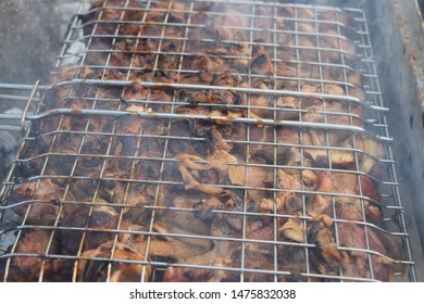Large stainless steel barbecue racks filled with fresh raw diced meat