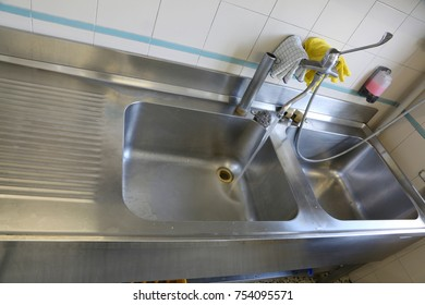 large stainless steel sink in an industrial kitchen for preparing meals in the canteen