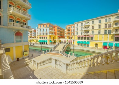 Large staircase leading to a Venetian bridge on canals of picturesque Qanat Quartier icon of Doha, Qatar in a sunny day with blue sky. Venice at the Pearl-Qatar, Persian Gulf, Middle East.