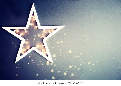 A large  star with lots of lights burning  over dark stone background. Christmas star