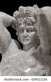 A large statue of a gray marble stone a man atlas holding the sky