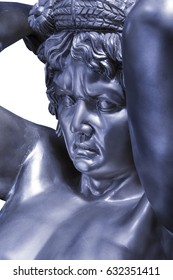 Large statue of steel metal atlas man holding sky