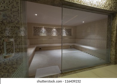 Large steam room with glass door in health spa at a luxury hotel