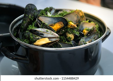 A large steaming pot with steamed mussels, fresh herbs and vegetables. Mussels are highly popular seafood menu in Belgium. Belgian style.