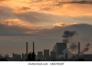 Large steel factory at sunset in Romania. Smoking factory chimneys. Environmental problem of pollution of environment and air in large cities. View of large plant