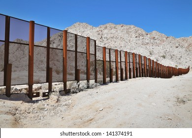 Large steel fence protecting the border between Mexico and the United States of America at the Tinajas Altas Mountains in Arizona (Sonoran Desert). Common place for illegals & drug smugglers to cross.