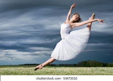 large step of beautiful ballet dancer against cloudy sky