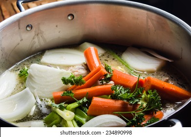 A large stock pot on a stove with vegetables cut for making soup