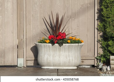 A large, stone flower planter outside a residential home/Large Outdoor Flower Planter/A large, stone flower planter outside a residential home.