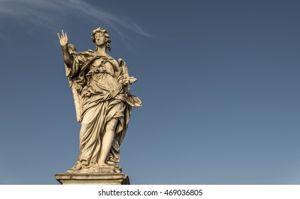 A large, stone statue of an angel, against a deep blue summer sky
