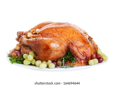 A large a stuffed turkey on a platter garnished with grapes.