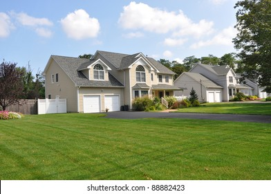 Large Suburban Cape Cod McMansion Home in Residential District Daytime Blue Cloud Sky