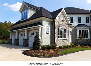 Large suburban house exterior with tree car garage