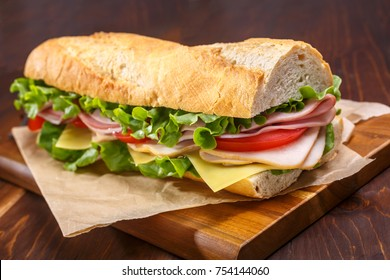 Large subway baguette sandwich cut in half filled with ham, turkey breast, cheese, lettuce and tomatoes on a cutting board closeup.