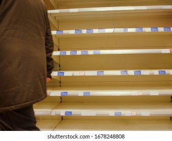 large supermarket sold out of stock with a person walking by the shelves