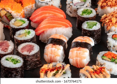 Large sushi set, close-up on a black background. An assortment of various maki, nigiri and rolls