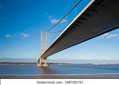 Large suspension bridge spanning a wide river estuary on a clear day with blue sky and clouds