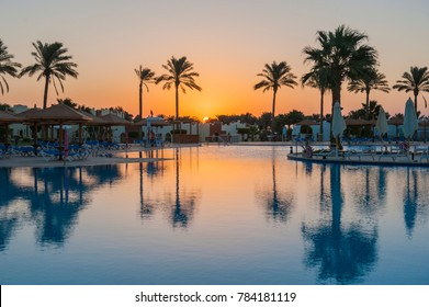 Large swimming pool in a luxury tropical hotel resort at dawn sunrise with palm trees