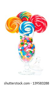 Large swirled lollipops displayed in an apothecary jar full of bubble gum.  Shot on white background.