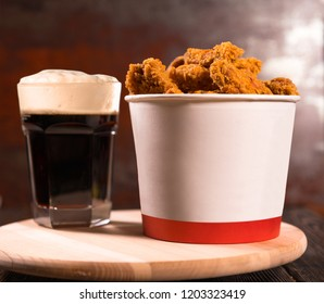 Large takeaway tub of fried chicken nuggets served with a glass of frothy beer on a wooden board