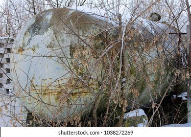 A large tank for collecting milk near a stone fence in the abandoned and destroyed factory on the background of white snow in winter. Ruin and vandalism.