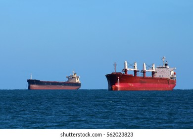 A large tanker or frigate anchored in the ocean near a port or harbor.