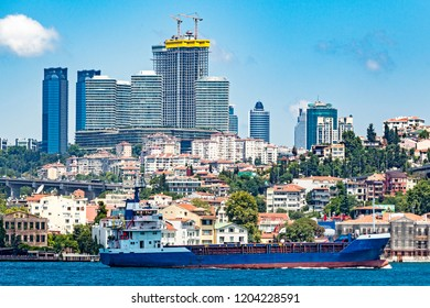 A large tanker ship travels up the Bosporus Strait with large modern skyscrapers being constructed in the background in Istanbul, Turkey.