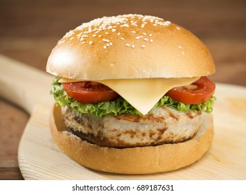 Large tasty burger with meat on wooden table.