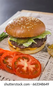 A large tasty burger with sliced tomato on a table