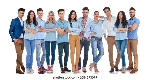 large team of casual men and women standing together on white background, looking confident and excited.