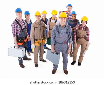 Large team of diverse artisans standing grouped together with their tools and hardhats lead by a handsome smiling foreman  high angle isolated on white