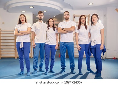 large team, group of physical therapists  workers posing, work room indoors.