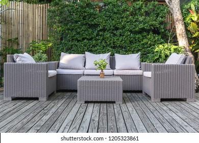 Grand patio terrasse avec mobilier de jardin en rotin dans le jardin sur parquet.
