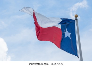 Large Texas (The Lone Star) flag waving on flag pole with cloud blue sky. Windy and sunny day with waving flag blowing/flowing. Ruffled Texas flag. Room for text, copy space.