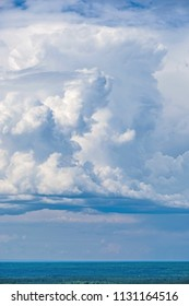 A large thunderhead or cumulonimbus cloud rolls over the landscape.