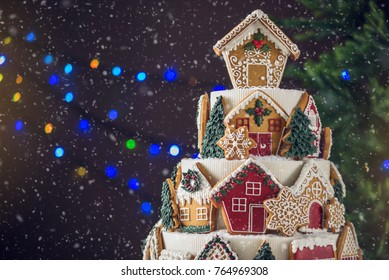 Large tiered Christmas cake decorated with gingerbread cookies and a house on top. Tree and garlands in the background. The concept of The desserts for the new year