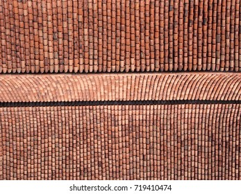 large tiled roof from above with rows and ridges in orange terracotta colors background