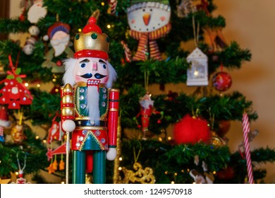 Large tin nutcracker soldier on a Christmas tree with blurred background. Seasonal toy figure before an illuminated artificial Christmas tree with lights and colorful decorations.